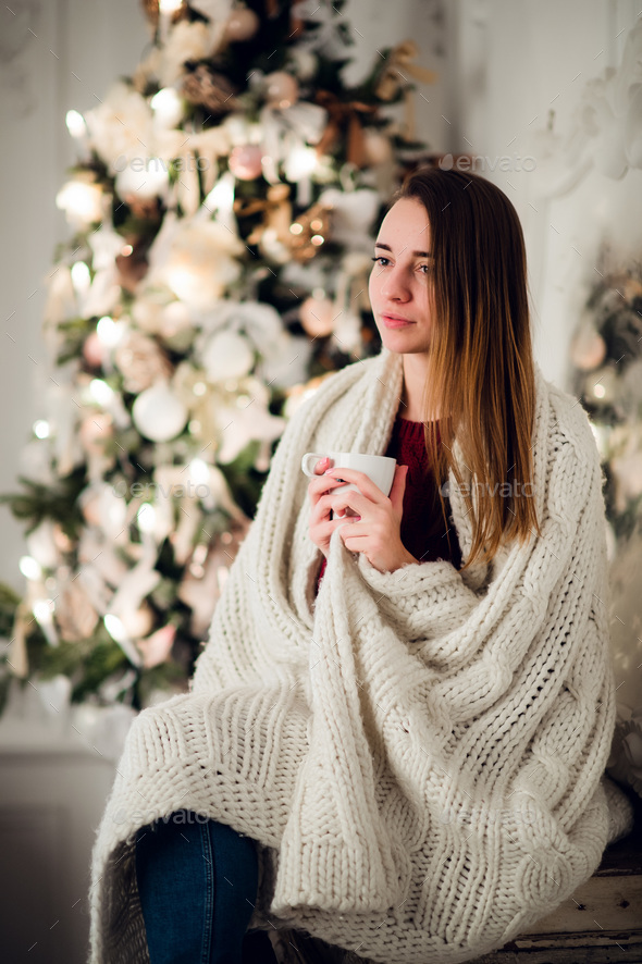 Happy young woman with cup of hot beverage near christmas tree - Stock Photo - Images