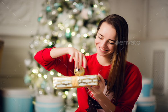 Portrait of beautiful woman with gift sitting by Christmas tree at home - Stock Photo - Images