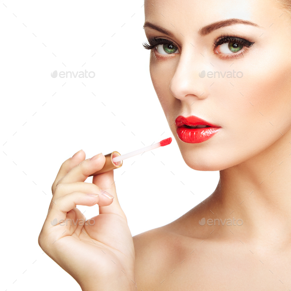 Beautiful young woman paints lips with lipstick. Perfect make-up - Stock Photo - Images