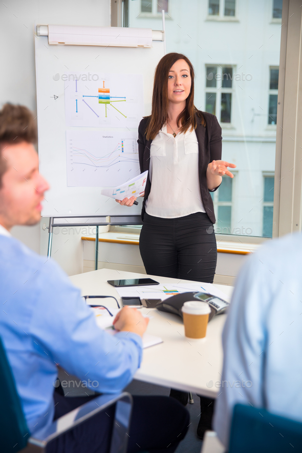Female Professional Giving Presentation To Colleagues - Stock Photo - Images