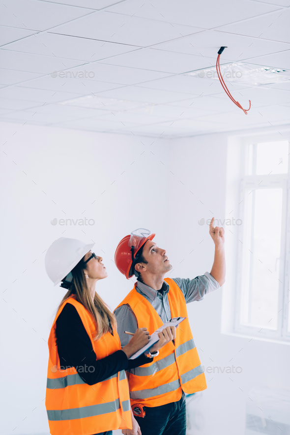 Maintenance Engineers checking cables for fire alarm - Stock Photo - Images
