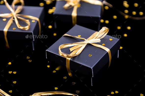 Black gift boxes with gold ribbon on shine background. Close up. - Stock Photo - Images
