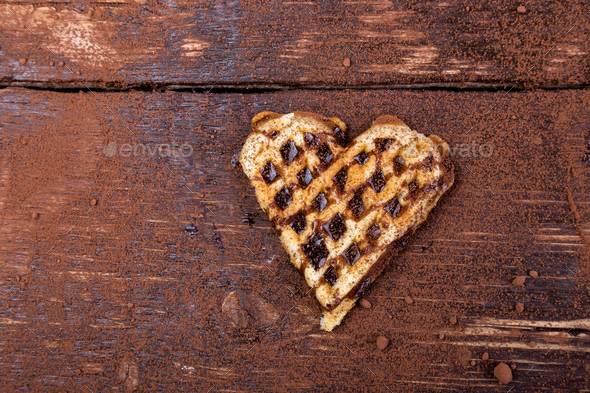 One belgian heart shaped waffle with chocolate on wooden background. Flat lay. Copy space - Stock Photo - Images
