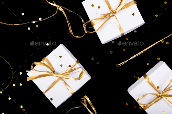 White gift boxes with gold ribbon on shine background. Flat lay - Stock Photo - Images