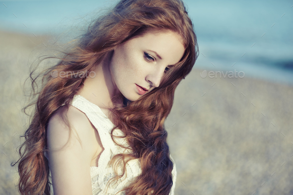 Beautiful woman with red hair at the sea - Stock Photo - Images