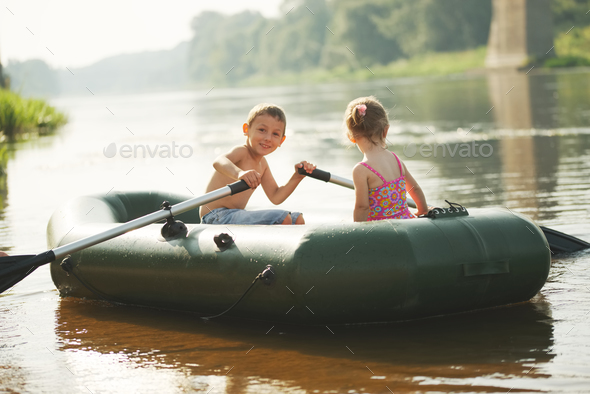 happy boy swimming in fishing boat - Stock Photo - Images
