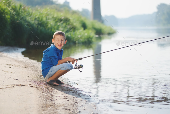 happy boy with rod on coast of river - Stock Photo - Images