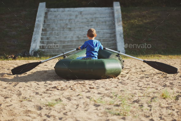little boy swimming in boat on sandy beach - Stock Photo - Images