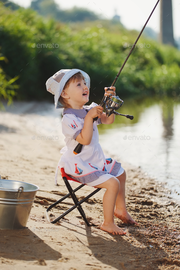 happy girl with rod on coast of river - Stock Photo - Images