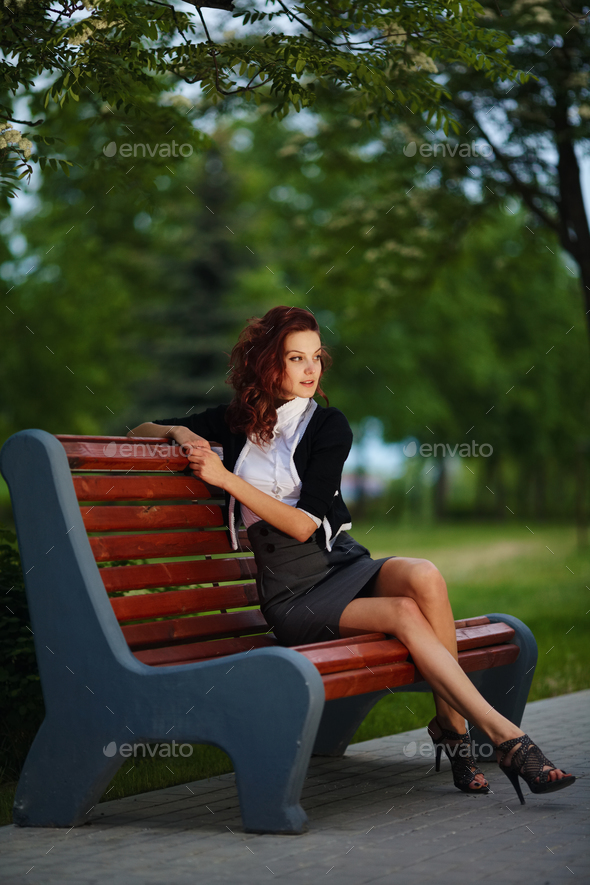 beautiful girl sitting on bench in park - Stock Photo - Images