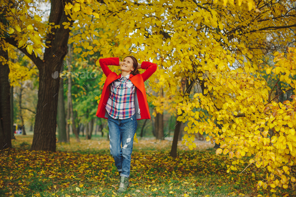 Girl with long wavy hair enjoying autumn in the park. - Stock Photo - Images