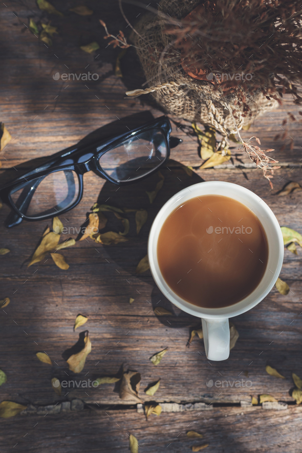 Cup of coffee with eyeglasses on old wooden tabl - Stock Photo - Images
