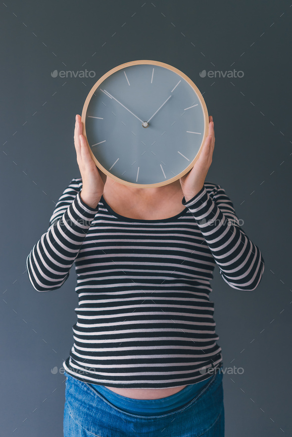 Pregnant female with vintage alarm clock - Stock Photo - Images