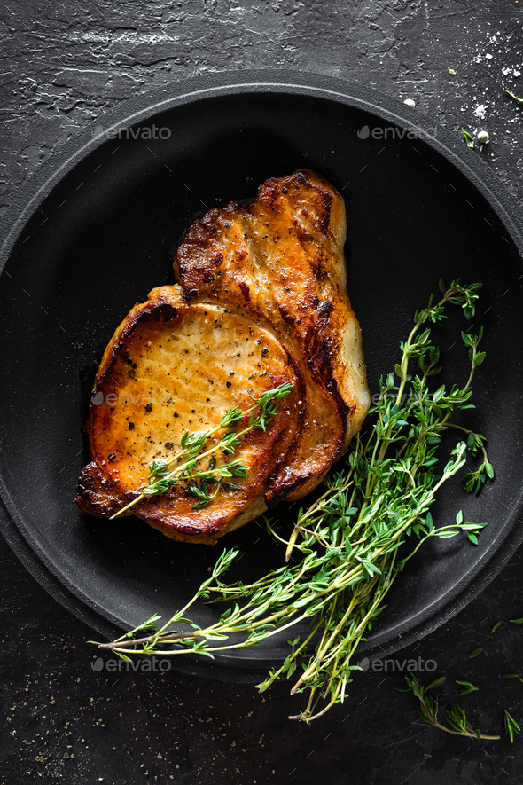 Pork meat, grilled steak on black background, top view - Stock Photo - Images