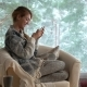 A Woman Uses a Smartphone Sitting in a Cozy Living Room  - VideoHive Item for Sale