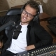 Radio Presenter in Glasses Speaks Into Microphone Beside Mixing Console - VideoHive Item for Sale