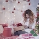 Young Beautiful Woman Sits on a Bed Near a Christmas Tree and Wraps a New Year Gift - VideoHive Item for Sale