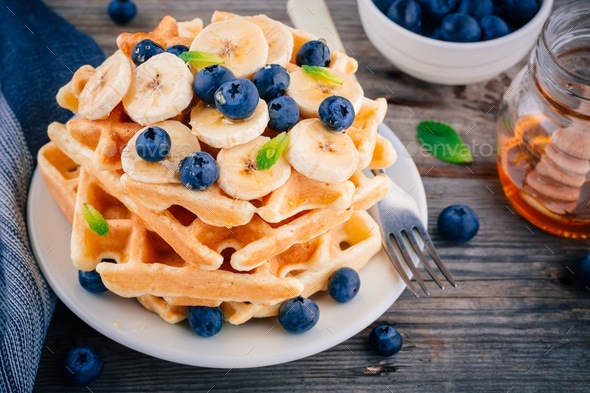 Fresh homemade waffles with blueberries and banana for breakfast - Stock Photo - Images