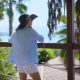 Woman Standing on Terrace of Tropical Hotel on Ocean Coastline
