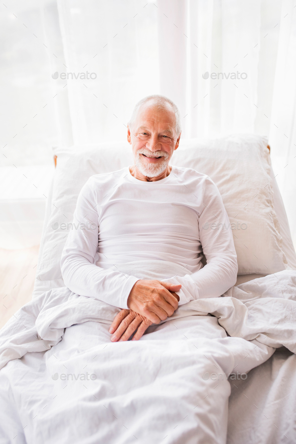 Senior man lying in bed at home. - Stock Photo - Images