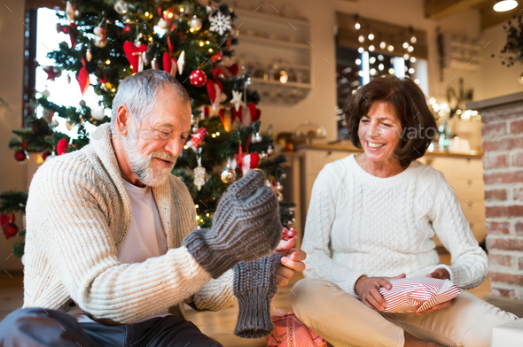 Senior couple in front of Christmas tree enjoying presents. - Stock Photo - Images