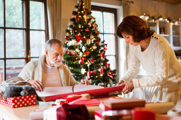 Senior couple in sweaters wrapping Christmas gifts together. - Stock Photo - Images