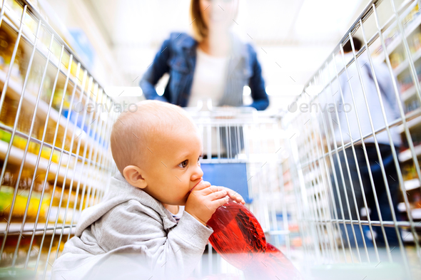 Young mother with her little baby boy at the supermarket. - Stock Photo - Images