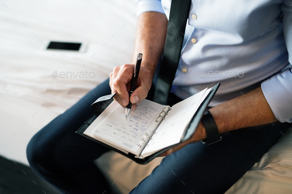 Mature businessman making notes in a hotel room. - Stock Photo - Images