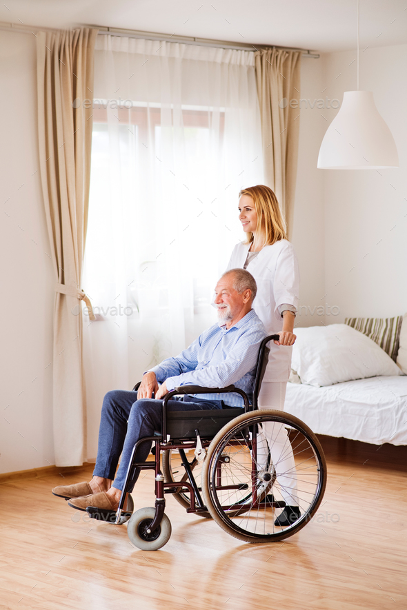 Nurse and senior man in wheelchair during home visit. - Stock Photo - Images