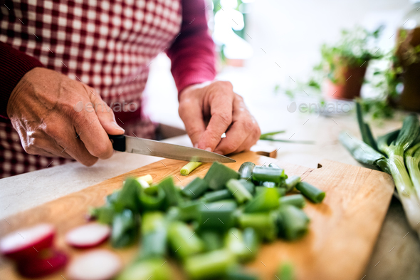 A senior man preparing food in the kitchen. - Stock Photo - Images