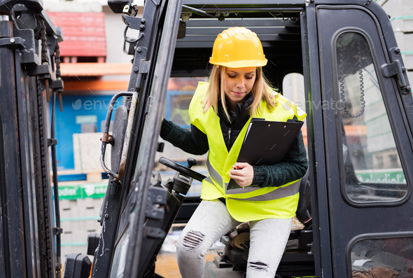 Female forklift truck driver outside a warehouse. - Stock Photo - Images