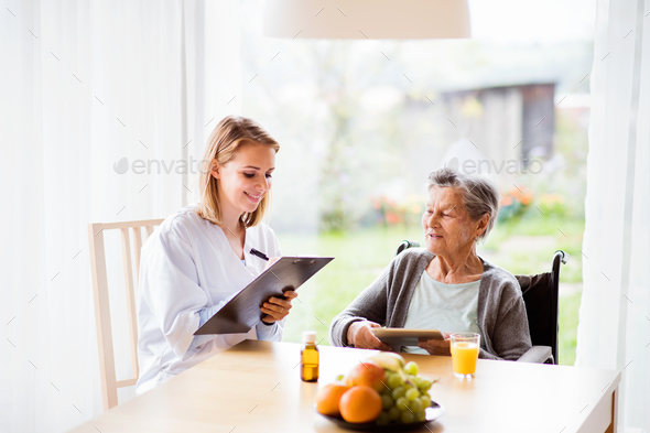 Health visitor and a senior woman with tablet. - Stock Photo - Images