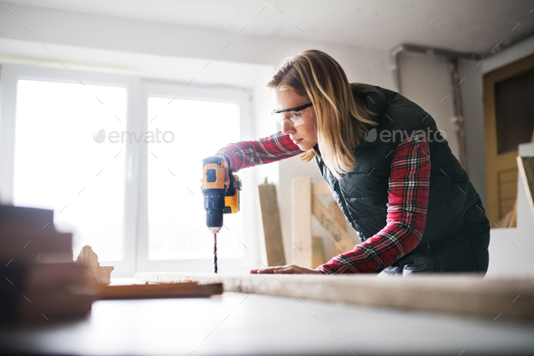 Young woman worker in the carpenter workroom. - Stock Photo - Images