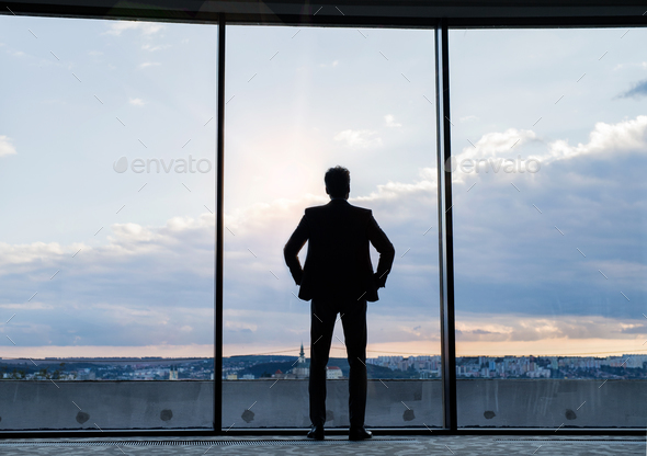 Mature businessman standing at the window in a hotel. - Stock Photo - Images