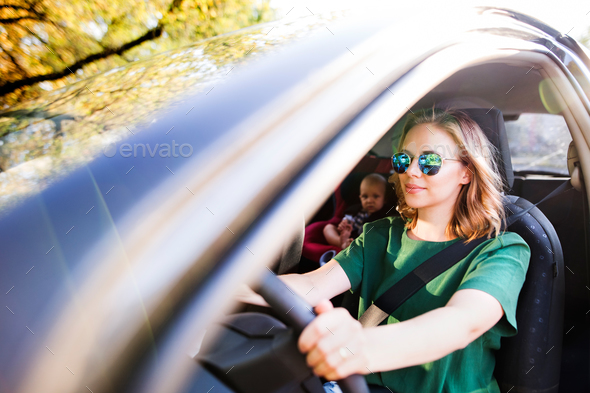 Young mother with her little baby boy in the car. - Stock Photo - Images