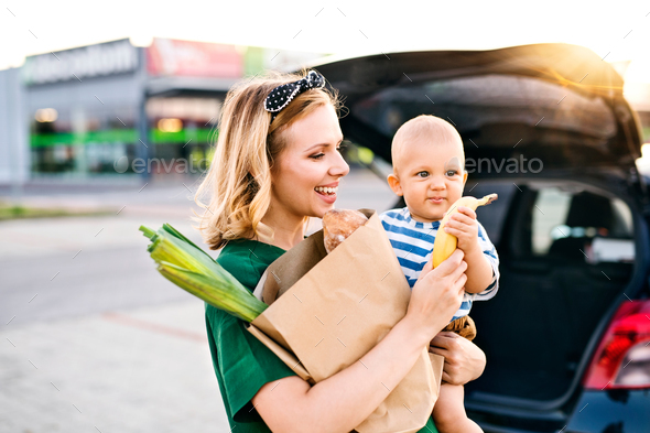 Young mother with baby boy in front of a supermarket. - Stock Photo - Images