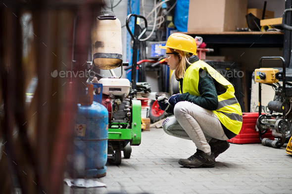 Young female worker in a warehouse. - Stock Photo - Images