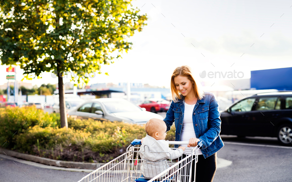 Mother with baby boy going shopping in the car park. - Stock Photo - Images