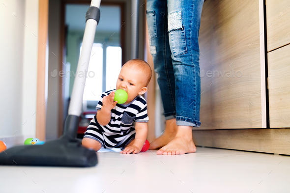 Young mother with a baby boy doing housework. - Stock Photo - Images
