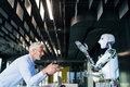 Mature businessman or a scientist with robot. - PhotoDune Item for Sale