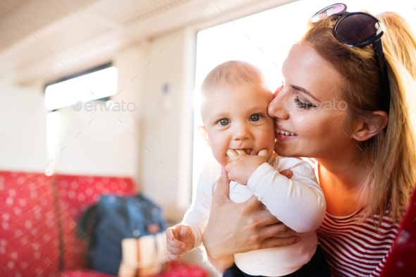 Young mother travelling with baby by train. - Stock Photo - Images