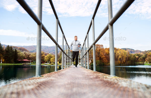 Young athlete with smartphone running in park in autumn. - Stock Photo - Images