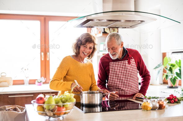 Senior couple preparing food in the kitchen. - Stock Photo - Images