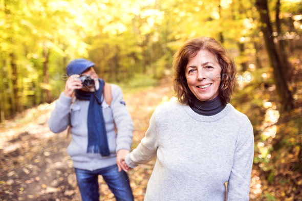 Senior couple on a walk in autumn forest. - Stock Photo - Images