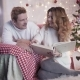 Young Beautiful Looking at Photo Album on Bed Near Christmas Tree - VideoHive Item for Sale