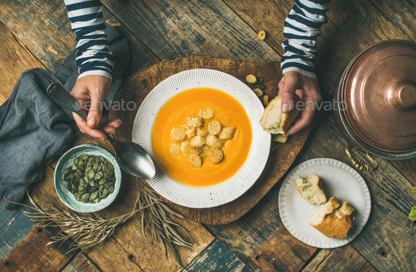 Fall warming pumpkin cream soup with seeds and bread - Stock Photo - Images