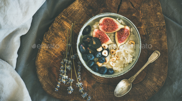 Rice coconut porridge with figs, berries and hazelnuts in bowl - Stock Photo - Images