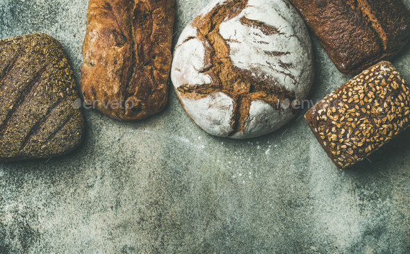 Top view of rustic bread loaves over grey background - Stock Photo - Images