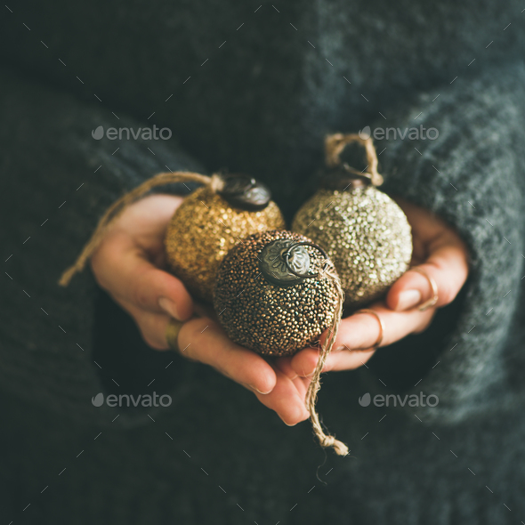 Woman holding golden and silver toy balls in hands - Stock Photo - Images
