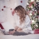 Young Beautiful Woman Types on a Laptop on a Bed Near a Christmas Tree - VideoHive Item for Sale